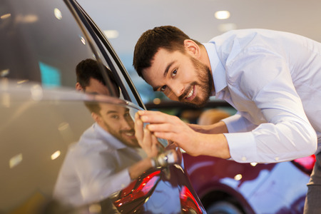 car clean: auto business, car sale, consumerism and people concept - happy man touching car in auto show or salon