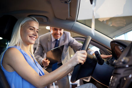 test drive: auto business, car sale, consumerism and people concept - happy woman with car dealer in auto show or salon Stock Photo