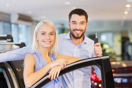 buying: auto business, car sale, consumerism and people concept - happy couple buying car in auto show or salon