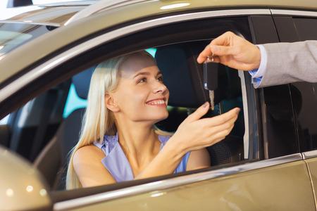 Autogeschäft, Autoverkauf, Verbraucherschutzbewegung und Leutekonzept - glückliche Frau, die Autoschlüssel vom Händler in der Automobilausstellung oder im Salon nimmt Standard-Bild - 36667767