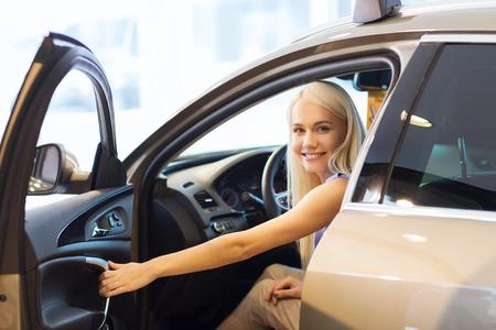 autozaken, auto verkoop, consumentisme, het transport en de mensen concept - tevreden vrouw zittend in of rijdende auto Stockfoto