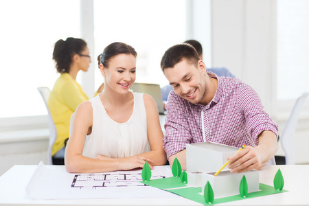 creating: startup, education, architecture and office concept - smiling architects with house model and blueprint working in office Stock Photo