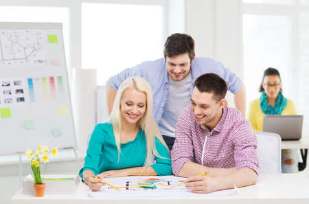 samples: education, interior design and office concept - smiling interior designers with color samples and blueprint in office Stock Photo