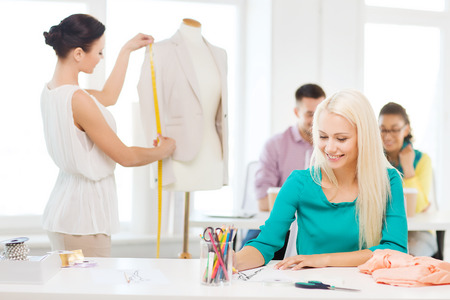 international students: startup, education, fashion and office concept - smiling designers drawing sketches and measuring jacket on mannequin in office