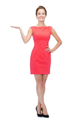 nice looking: advertising and people concept - smiling young woman in red dress holding something on palm of her hand