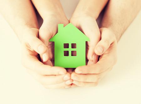 foto de primer plano de la mujer y el hombre manos que sostienen la casa verde