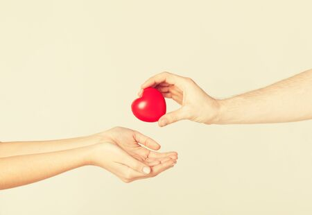 life giving birth: close up of man hand giving heart to woman