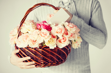 close up of man holding basket full of flowers and postcard. photo