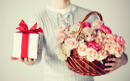close up of man holding basket full of flowers and gift box. Фото со стока