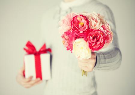 anniversario matrimonio: Close up di uomo che tiene bouquet di fiori e confezioni regalo.