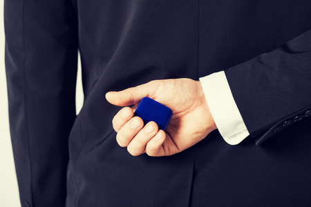 picture of man with gift box in suit holding a ring box photo