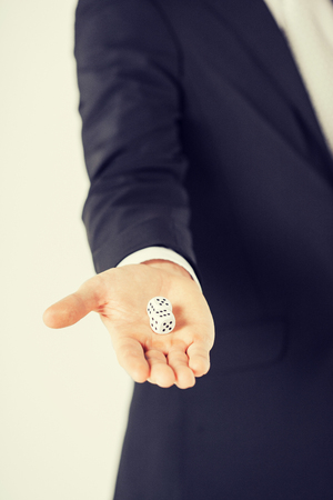 bad fortune: close up of mans hand holding white casino dice