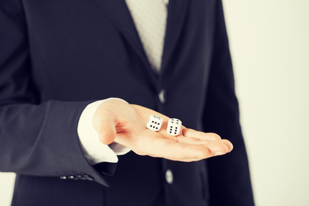 close up of mans hand holding white casino dice