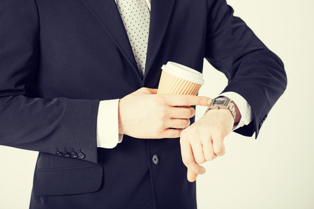 wasting away: close up of man with take away coffee looking at wristwatch