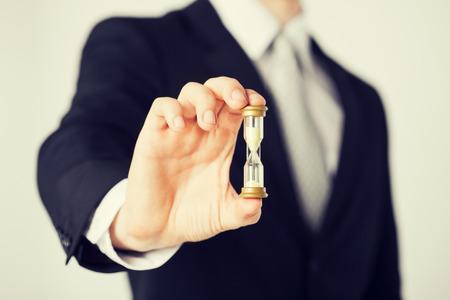 gestion del tiempo: Close up de la mano del hombre celebraci�n de reloj de arena. Foto de archivo