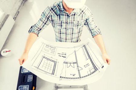 renovation house: male architect in helmet with blueprint