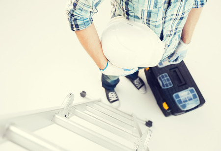 setup man: man with ladder, helmet and toolkit Stock Photo