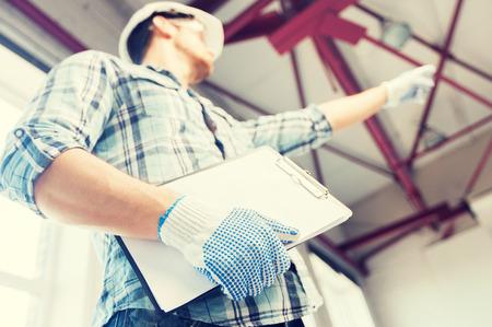 ingeniero: hombre en el casco y los guantes con hoja de ruta en la fábrica