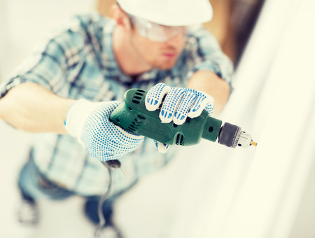 man in helmet with electric drill making hole in wall