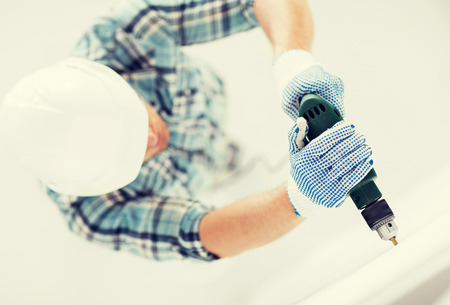 making hole: man in helmet with electric drill making hole in wall