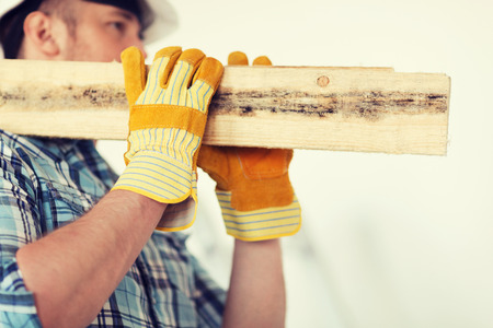 shoulder carrying: repair, building and home concept - close up of male in gloves and helmet carrying wooden boards on shoulder Stock Photo