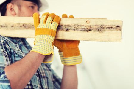 reparatie, bouw en huis concept - close-up van een man in handschoenen en helm dragen houten planken op de schouder Stockfoto