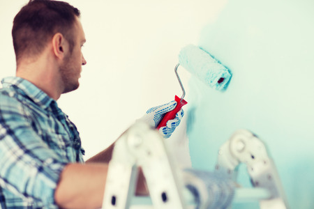Home repair: close up of male in gloves holding painting roller