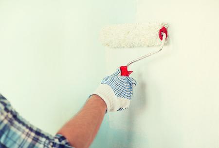 pintor: cerca del var�n en los guantes que pintan la pared con el rodillo