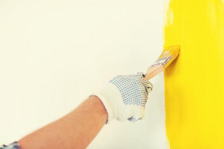 herramientas de construccion: reparación, construcción y concepto de hogar - cerca del varón en los guantes con el pincel