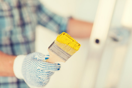 wall paintings: repair, building and home concept - close up of male in gloves holding paintbrush Stock Photo