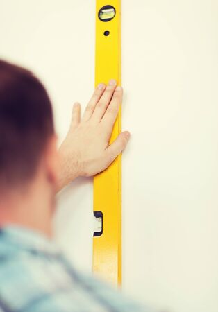 close up of male with spirit level measuring wall photo