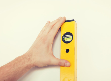 renovating: close up of male with spirit level measuring wall