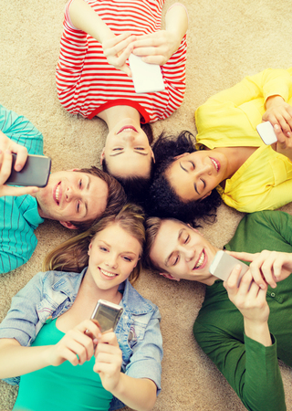 group of young smiling people lying down on floor in circle with smartphones photo