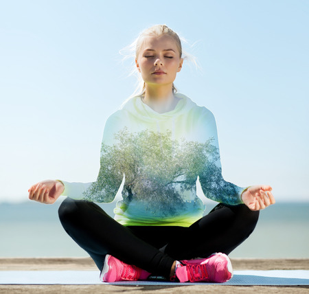 happy young woman meditating in lotus pose over blue sky with sea and tree background Imagens