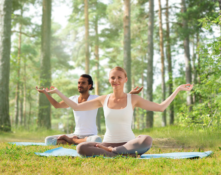 team lotus: smiling couple meditating and sitting on mats over green woods background