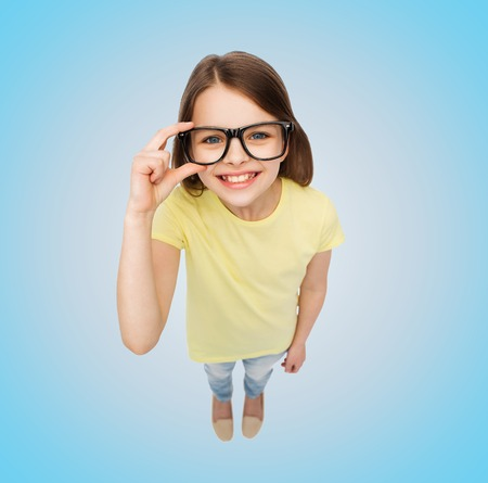 teenage problems: education, school, people, childhood and vision concept - smiling little girl in black eyeglasses over blue background Stock Photo