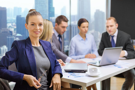 smiling businesswoman over team with laptop computer sitting in office