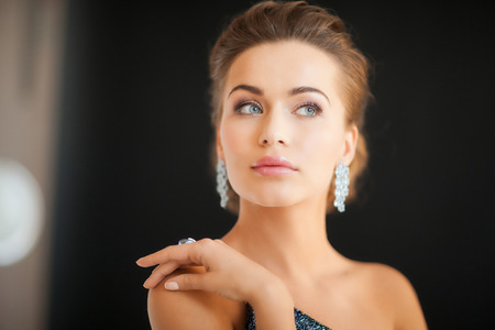 precious stone: beautiful woman in evening dress wearing diamond earrings