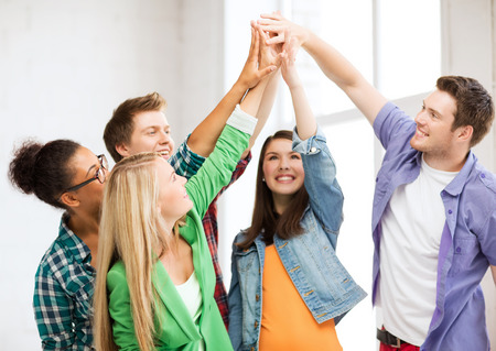 win: education and friendship concept - happy students giving high five at school