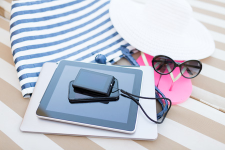 photo of accessories: close up of tablet pc, notebook, smartphone and summer accessories on beach Stock Photo