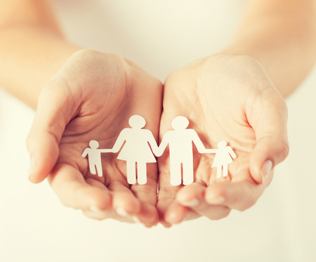 close up of womans cupped hands showing paper man family Foto de archivo