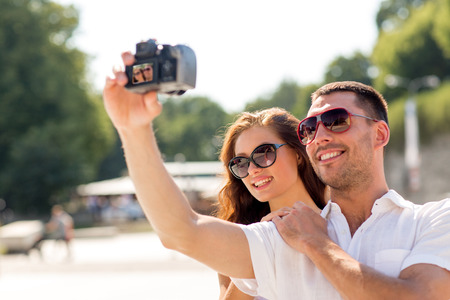 making love: smiling couple wearing sunglasses making selfie with digital camera in park Stock Photo