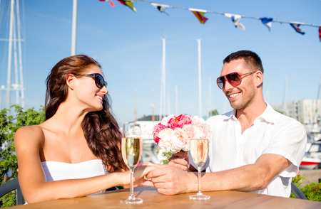 smiling couple wearing sunglasses with bunch of flowers and champagne glasses looking to each other at cafe photo