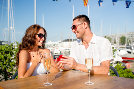 love, dating, people and holidays concept - smiling couple wearing sunglasses with champagne and small red gift box looking to each other at cafe photo