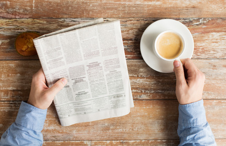 close up of male hands with newspaper, muffin and coffee cup on table