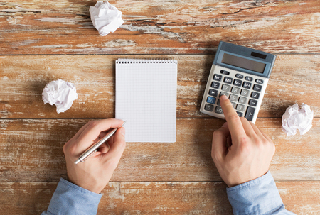 cramped space: close up of close up of male hands with calculator, cramped paper wads and notebook on table