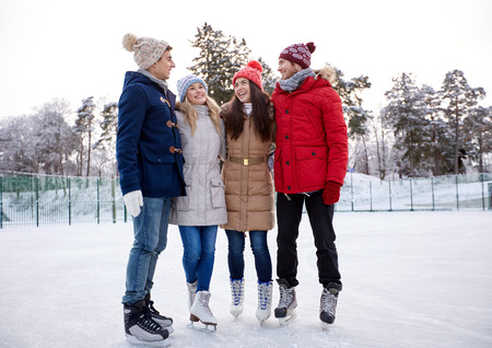 happy friends ice skating and hugging on rink outdoors photo