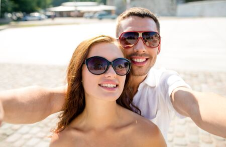 making face: smiling couple wearing sunglasses making selfie in city