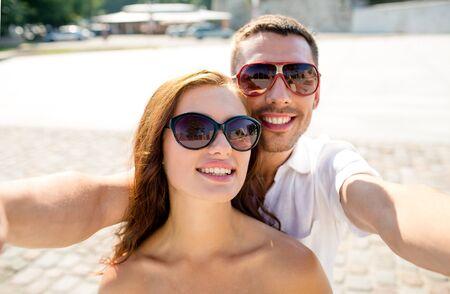 haciendo el amor: sonriendo par de gafas de sol que hacen Autofoto en la ciudad Foto de archivo