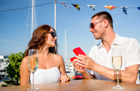 love, dating, people and holidays concept - smiling couple wearing sunglasses with champagne and red gift box looking to each other at cafe photo